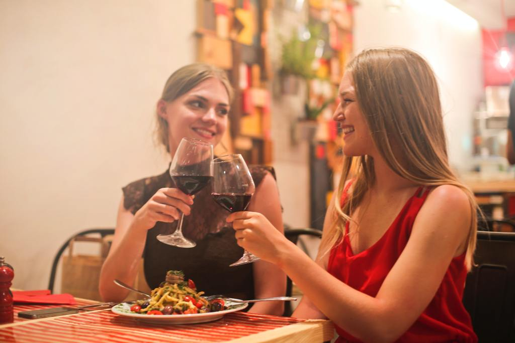 Female couple having an at home date involving wine and dinner