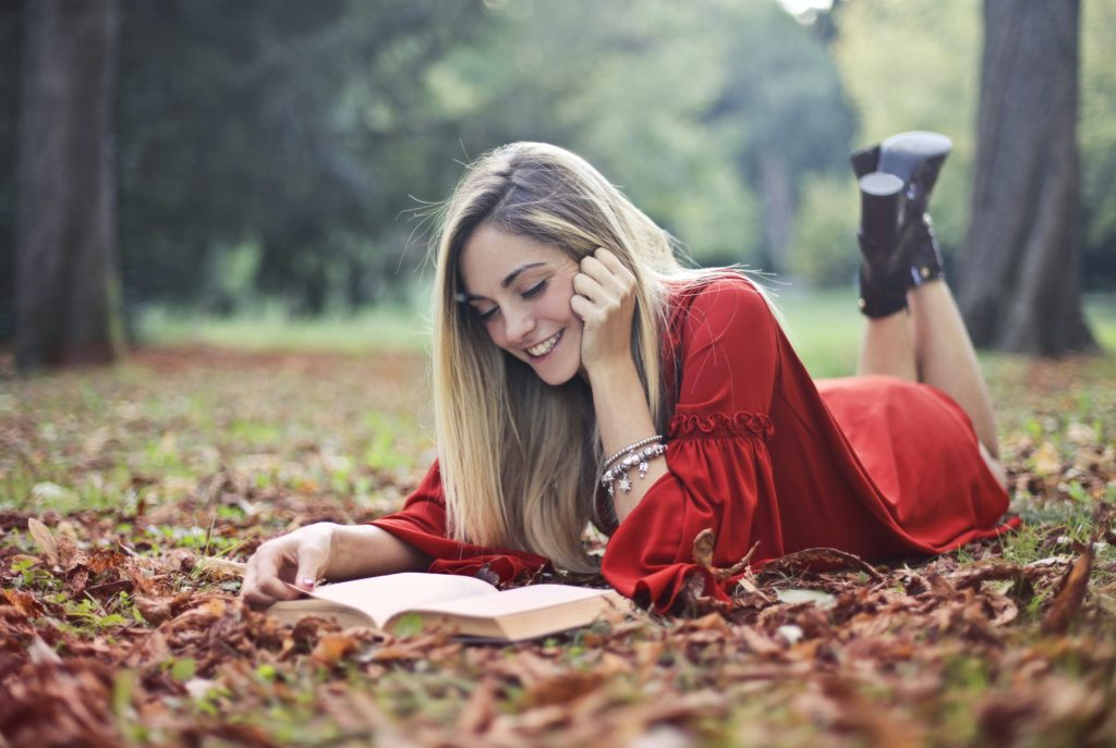 Woman Reading a Book Outside in the Fall