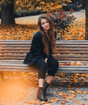 Woman sitting on bench in Fall