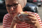 Frau mit Kopftuch und Tasse in der Hand blickt in die Kamera
