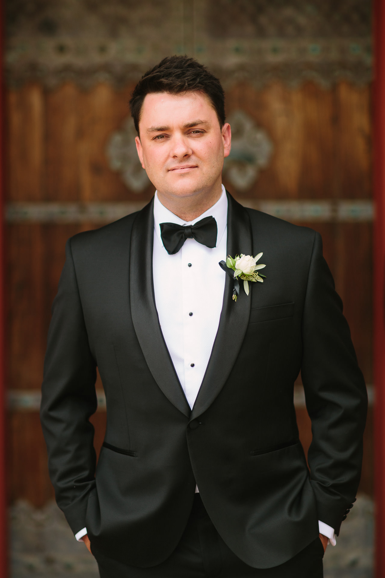 dapper groom in tuxedo, black tie against wooden door