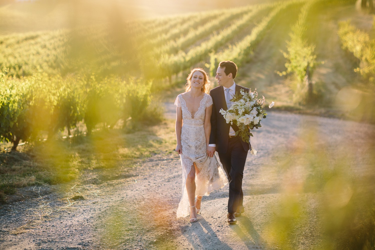 Coriole winery wedding Mclarenvale , bride and groom walking through backlit vines in golden afternoon light