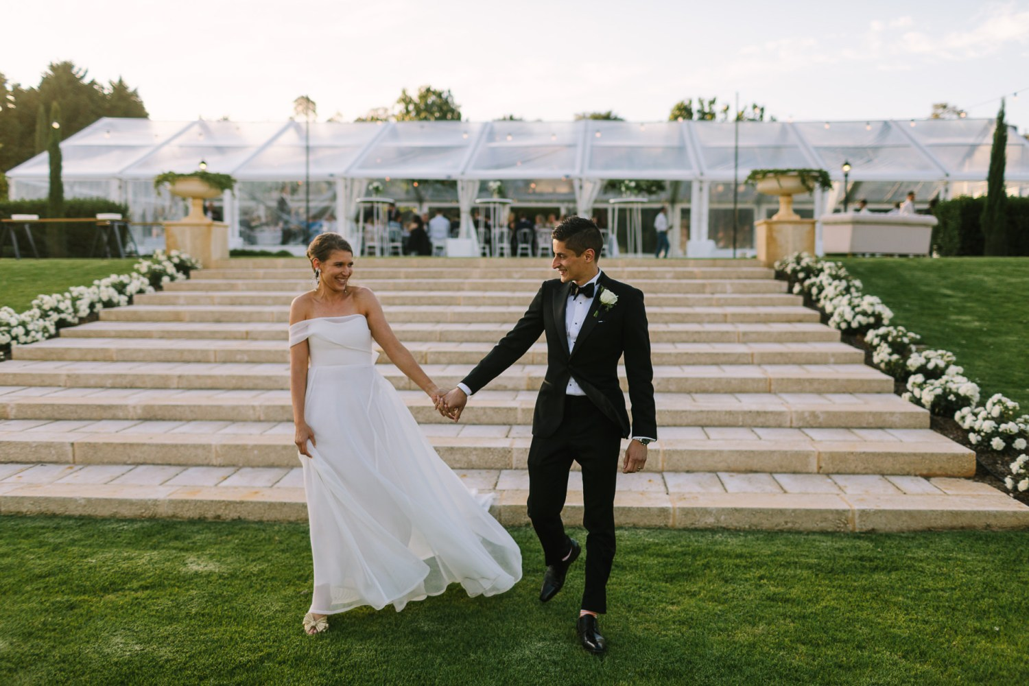 Bride wearing off the shoulder wedding dress and groom in black tuxedo walking away from their marquee reception down steps to get sunset photos at their wedding at Mandalay House and Garden in the Adelaide Hills