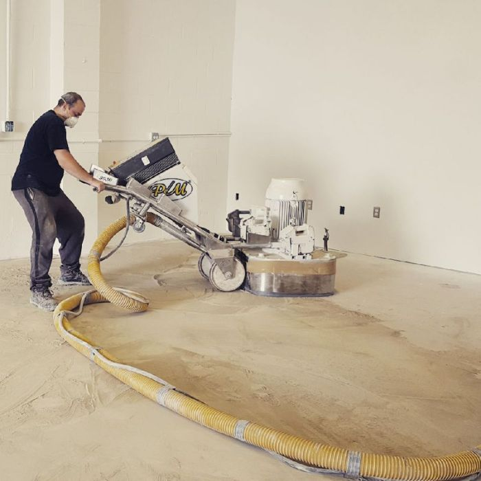 Two men diamond grinding a garage floor