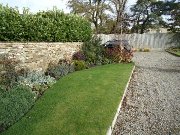 Lawn next to informal planting and gravel pathway