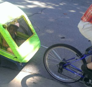 A bike trailer being pulled behind our bike