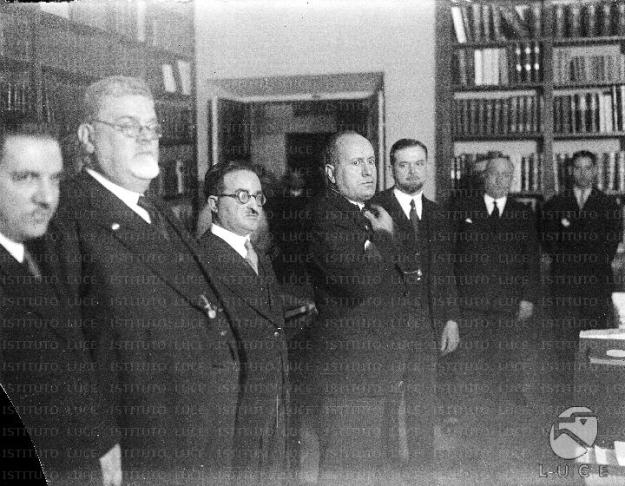 Mussolini sorpreso nella biblioteca dell'Istituto Treccani tra Giovanni Treccani, alla sua destra, Giovanni Gentile, Calogero Tumminelli, alla sua sinistra, ed altre personalità - Piano americano