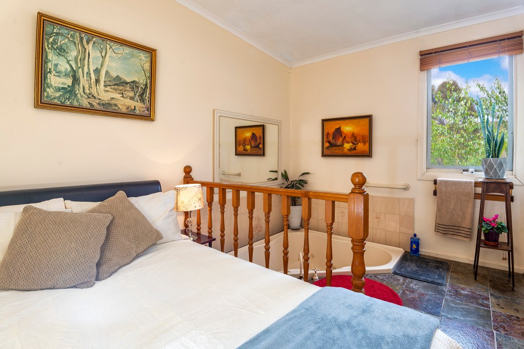 Bedroom 2 with a double bed and the two-person sunken spa bath