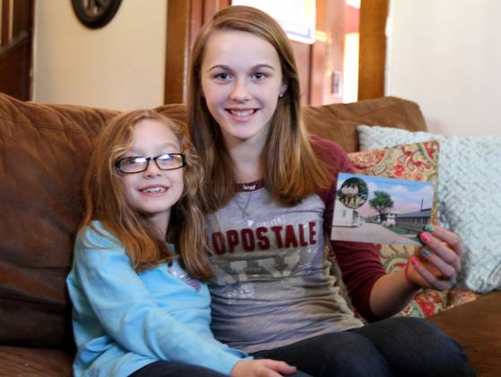 Sisters Madie, left, and Hannah Podgorny of Elmira, hold a postcard intended for two other sisters -- Pauline and Theresa Leisenring -- who once lived in their Bridgman Street home. (Photo: Jennifer Kingsley, (Elmira, N.Y.) Star-Gazette)