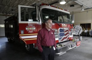 """In this March 20, 2013 photo, Greg Hull stands near a fire engine in the fire department garage in DuPont. Hull has announced his resignation, just days after state officials notified him they were stopping his pension following a review of his """"independent contractor"""" status with the south Pierce County city. (TED S. WARREN/AP) DuPont Fire Chief Greg Hull has announced his resignation, just days after state officials notified him they were stopping his pension following a review of his """"independent contractor"""" status with the south Pierce County city."""