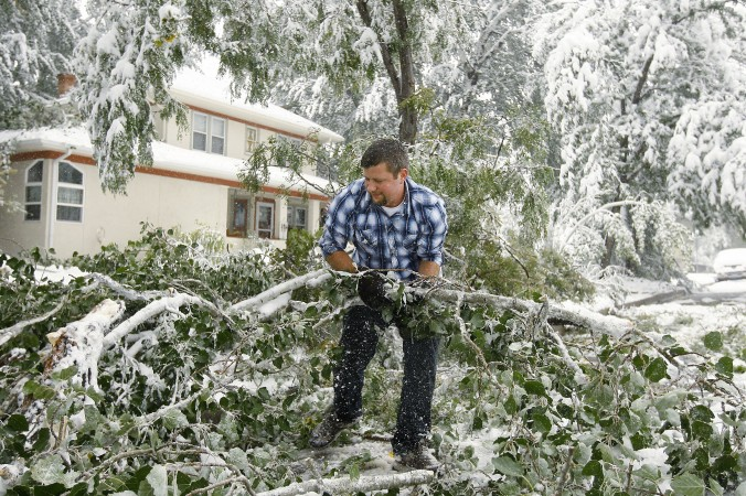 Thomas Leighton clears branches and tree limbs from the street in central Casper, Wyo. on Friday, Oct. 4, 2013. A major storm dumped heavy, wet snow over Wyoming, bringing down trees and power lines along the way. (AP Photo/Dan Cepeda, Casper Star-Tribune)