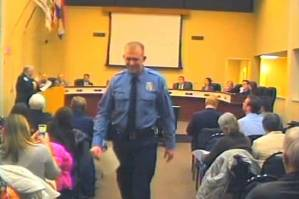 In this Feb. 11, 2014 image from video released by the City of Ferguson, Mo., officer Darren Wilson attends a city council meeting in Ferguson. (Credit: AP/City of Ferguson)