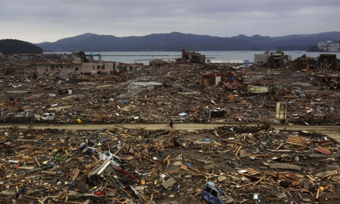 A Japanese survivor of the magnitude 9.0 earthquake rides his bicycle through the leveled city of Minamisanriku in 2011. Debris from the natural disaster continues to wash on to the US west coast. Photograph: David Guttenfelder/AP