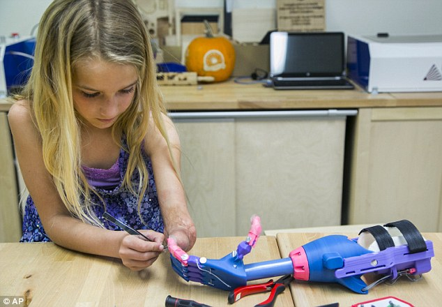 A new addition: Faith Lennox, 7, adjusts her newly 3-D printed hand which is the result of an emerging technology that is revolutionizing prosthetics
