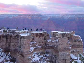 Visitors view the sunset at Mather Point on the South Rim after a dusting of winter snow. Credit: Mike Quinn, NPS photo.