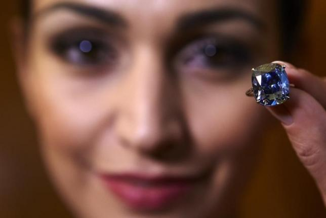 'Blue Moon Diamond' sells for world record $48.4 million - Sotheby's A model poses with a 12.03 carats cushion-shaped fancy vivid blue diamond mounted on a ring at Sotheby's auction house in Geneva, Switzerland November 4, 2015. REUTERS/Denis Balibouse