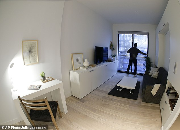 """In this Dec. 22, 2015, photo, Stage 3 Properties co-founder Christopher Bledsoe closes a sliding glass door as he stands at the Juliet balcony inside one of the apartment units at the Carmel Place building in New York. As the city-sponsored """"micro-apartment"""" project nears completion, it's setting an example for tiny dwellings that the nation's biggest city sees as an aid to easing its affordable housing crunch. (AP Photo/Julie Jacobson)"""