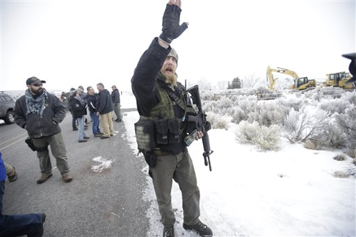 "A man standing guard pushes the media aside after members of the ""3% of Idaho"" group along with several other organizations arrived at the Malheur National Wildlife Refuge near Burns, Ore., on Saturday, Jan. 9, 2016. A small, armed group has been occupying the remote national wildlife refuge in Oregon for a week to protest federal land use policies. convoy oregon wildlife refuge(AP Photo/Rick Bowmer)"