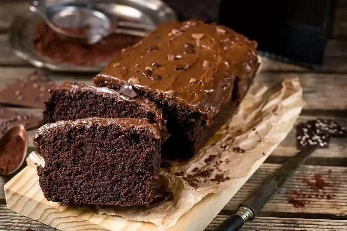 Um bolo de chocolate pequeno e duas partes dele á frente cortadas, em uma tábua de madeira