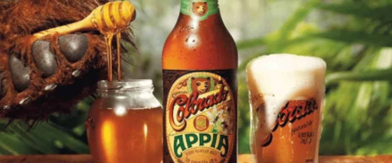 Garrafa de Colorado Appia ao lado de copo e jarro de mel - marcas de cerveja artesanal