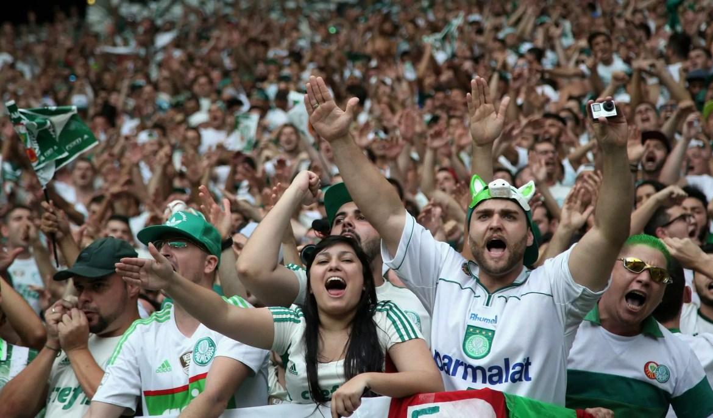Torcida do Palmeiras cantando, em destaque um mulher morena e um homem com uma touca de porco com os braços esticados e cantando