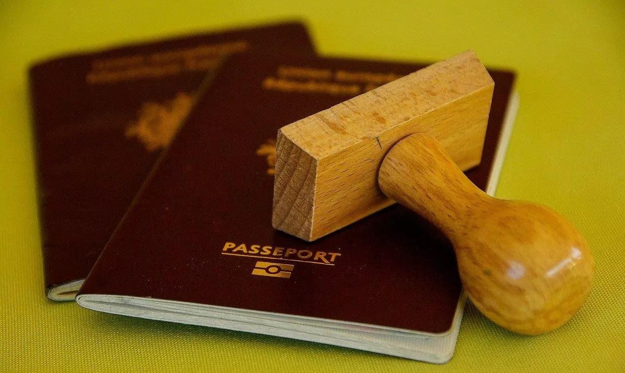 dois passaportes vermelhos, um sobre o outro, com um carimbo de madeira