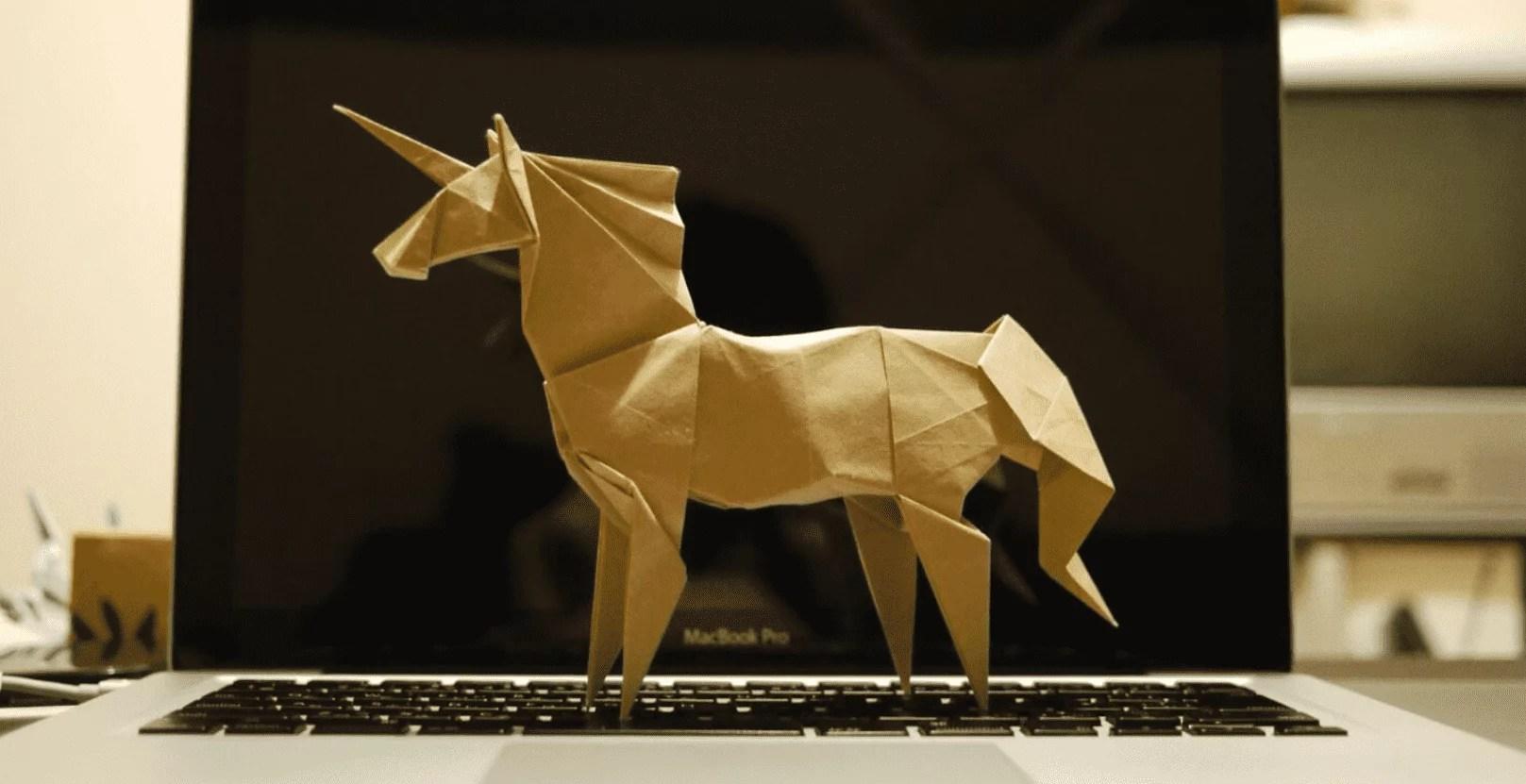 Imagem mostra um unicórnio feito de papelão, de lado e em cima de um notebook aberto.