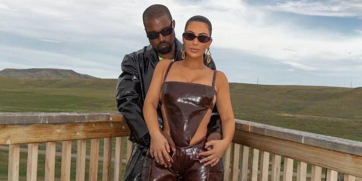 Kim Kardashian e Kanye West posados em um cerca de madeira