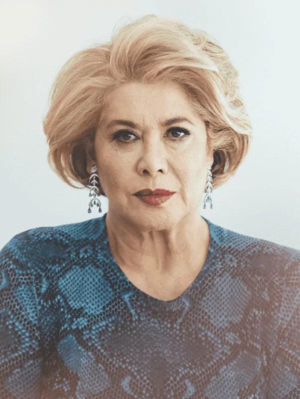 Foto da ex-milionária Patricia Kluge, mulher idosa, loira, usando brincos e um vestido azul.
