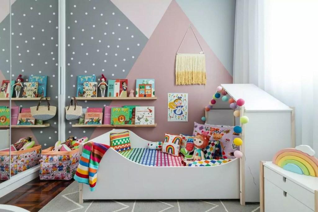 cama casinha com lençóis coloridos, luminária de bolinhas com livros infantis na parede