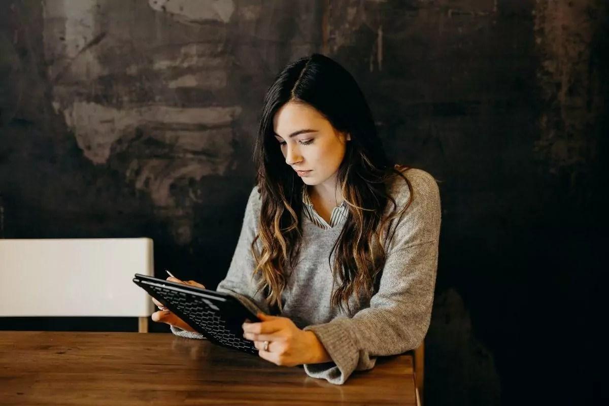 Imagem mostra mulher olhando tablet