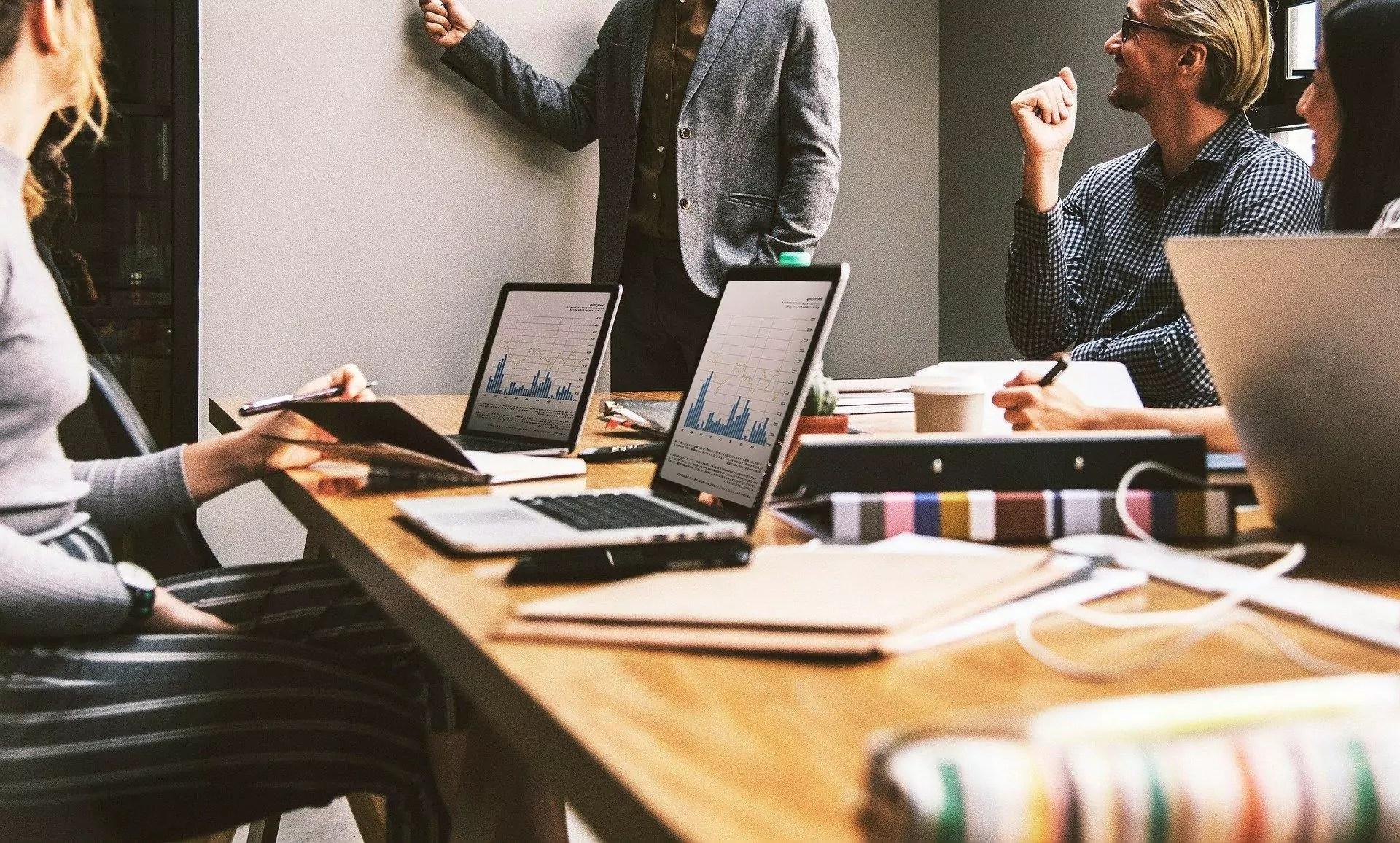 Mesa de reunião com notebook, planilhas e gráficos espalhados.