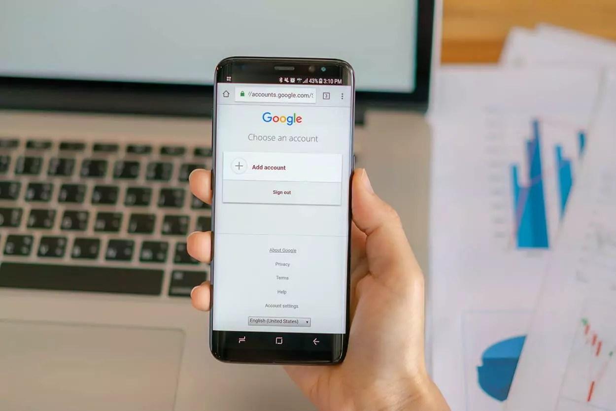 Homem segurando celular com conta Google