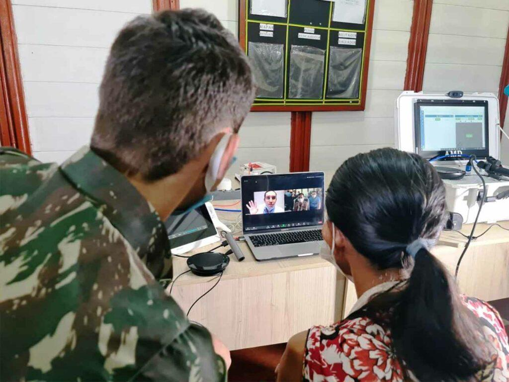 homem à esquerda e uma mulher à direita em consulta online por um computador