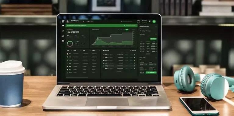 notebook com tela de trade em exchange de bitcoin, ao lado de um copo de café, iphone e phone de ouvido