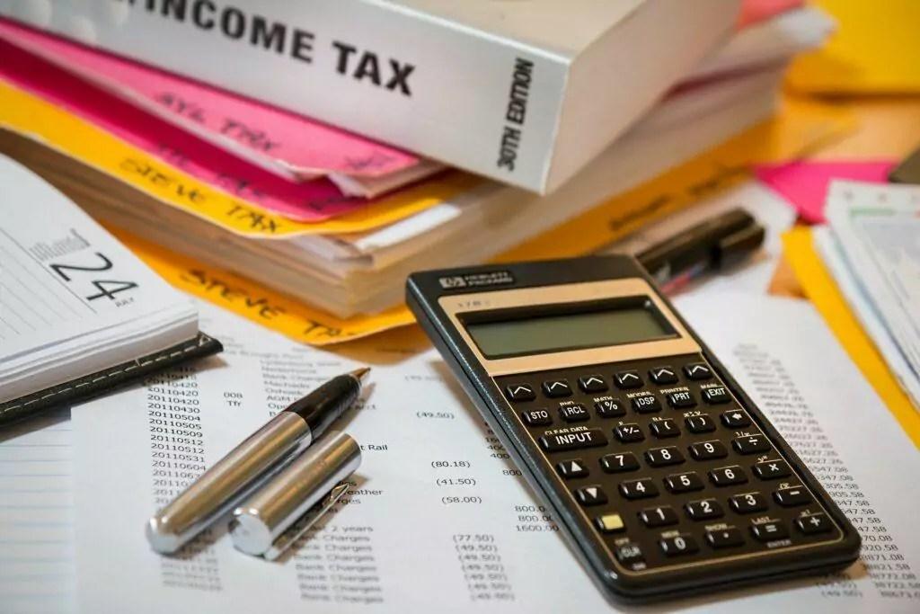mesa com calculadora, papéis e canetas