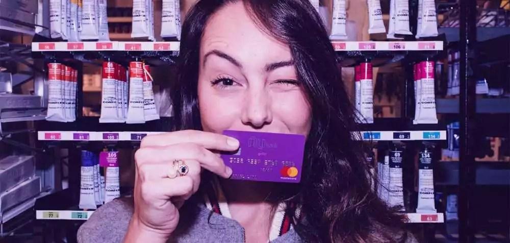 mulher segurando cartão de crédito do Nubank, piscando um olho