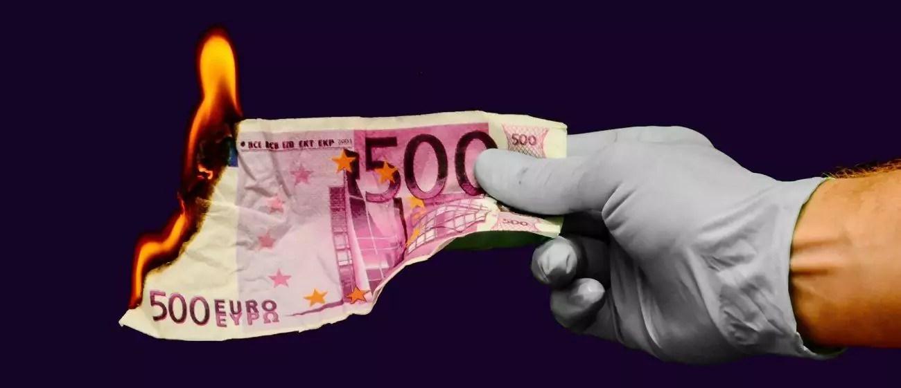 mão segurando cédula de dinheiro pegando fogo