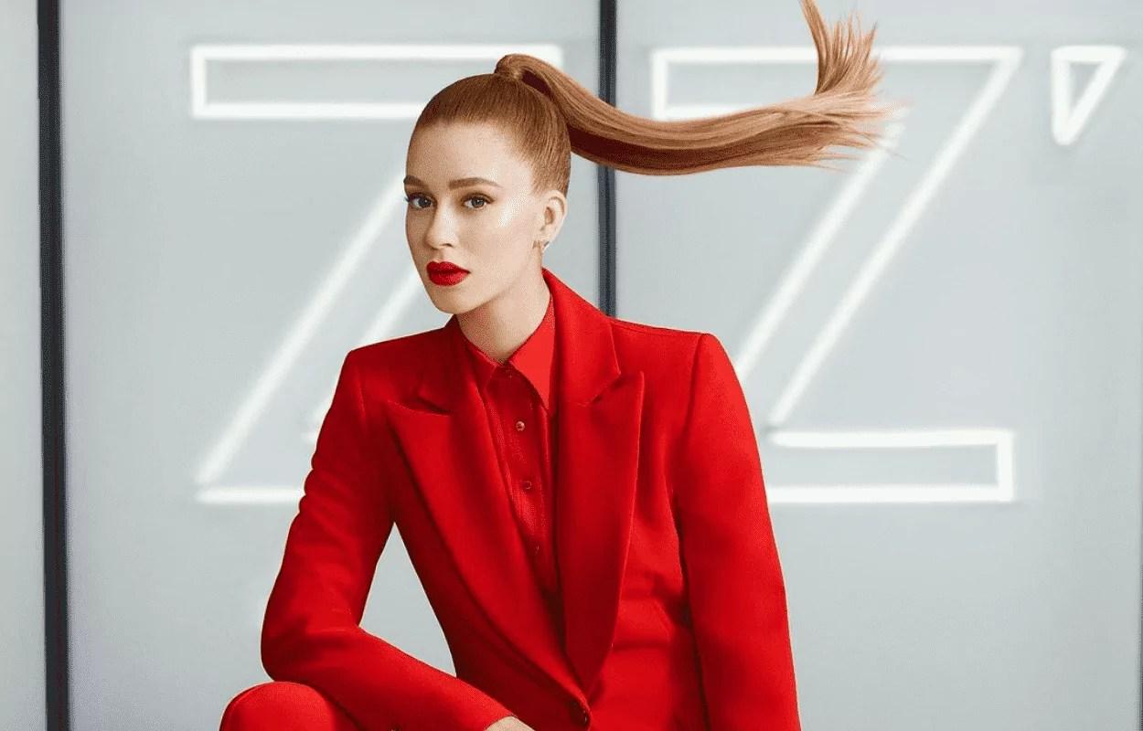 Imagem mostra Marina Ruy Barbosa com cabelos presos em rabo de cavalo e vestida com blazer vermelho