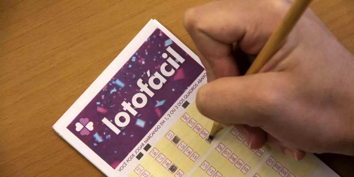 Lotofácil 2088 - a imagem mostra uma mão segurando um lápis e marcando números no volante da Lotofácil