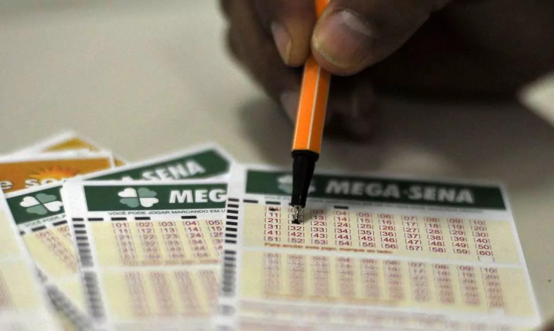 Mega Sena de ontem - A imagem mostra uma mão segurando uma caneta e marcando números no volante da Mega-Sena