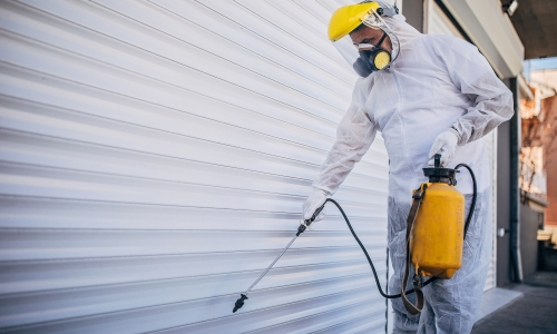 One man, man in protective suit, disinfecting and spraying garage doors outdoors.