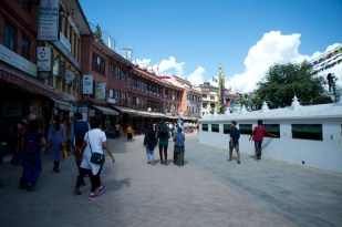 There are colorful houses, shops and restaurants in Boudhanath. On the right there are prayer wheels around the stupa.