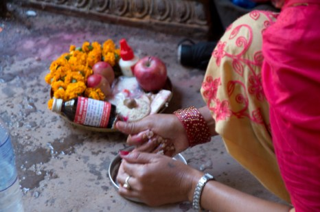 Lady preparing fferings to god - apple, flowers, rice