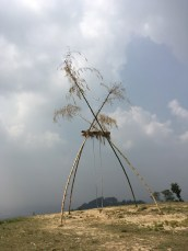 A large bamboo swing set up in the hilltop in a village.