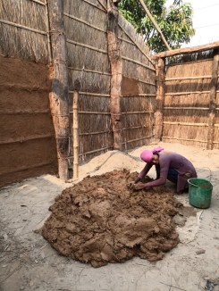 A Tharu woman using the mud and cow dung mixture to plaster the wall