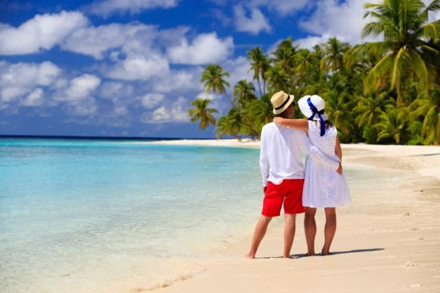 couple on beach enjoying their time after saving money with debt advisory services