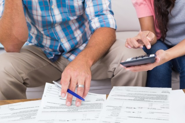 couple sat together on sofa dealing with their finances over paperwork