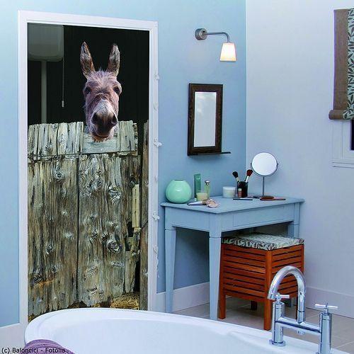 Vinilos para puertas con sentido del humor: un burro asoma su cabeza por encima de la puerta rústica de su cuadra y nos mira mientras estamos en casa.