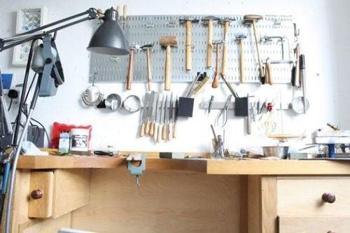 Ideas para ordenar herramientas de bricolaje en casa con un panel perforado de pared y un banco de trabajo.